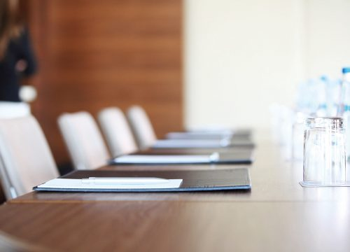 A meeting room with notepads and glasses with water