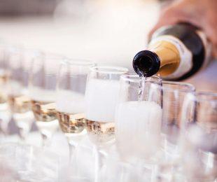 A person pouring champagne into glasses
