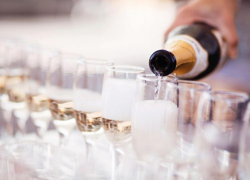 A person pouring champagne into glasses