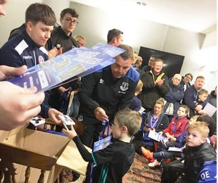 Everton coaches signing posters for children in the Vauxhall Sports Club