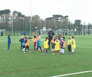 Everton coach training children on the 4k weather pitches