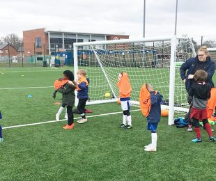 Children learning how to play football at the Vauxhall Sports Club