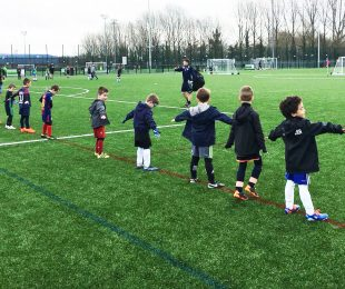 Children doing some warm ups in football camp on the football pitch