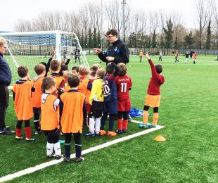 Coaches training children on the football pitch