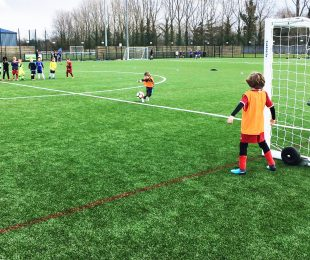 Child kicking a football doing a penalty shootout on the 4k weather pitch