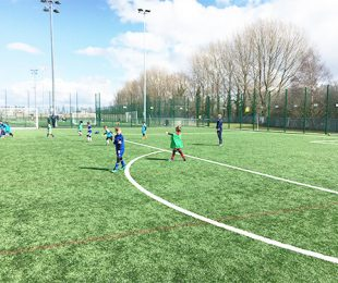 Children playing Football in the sun on a 4k weather pitch