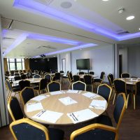 Seats surrounded by round tables setup for a corporate event