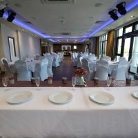 Tables and chairs with plates on the table ready for a wedding