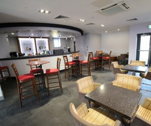 Bar stools and chairs around tables next to the bar in the function room