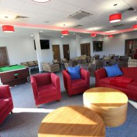 Chairs and sofas and a snooker table in the function room at Vauxhall Sports Club
