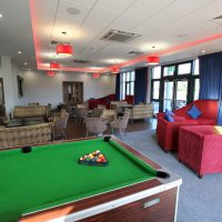 Pool table in lounge area with chairs and sofas