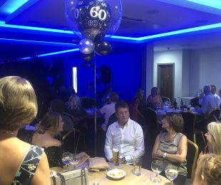 people sitting at tables celebrating a 60th birthday